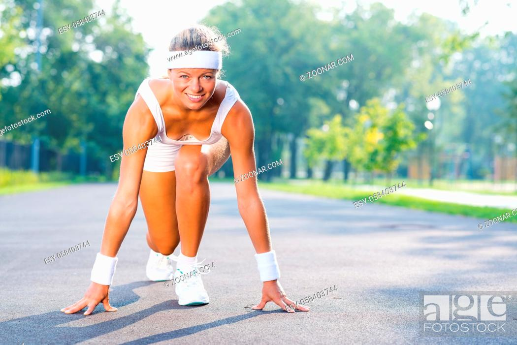 Stock Photo: Young woman runner outdoor standing in start pose.