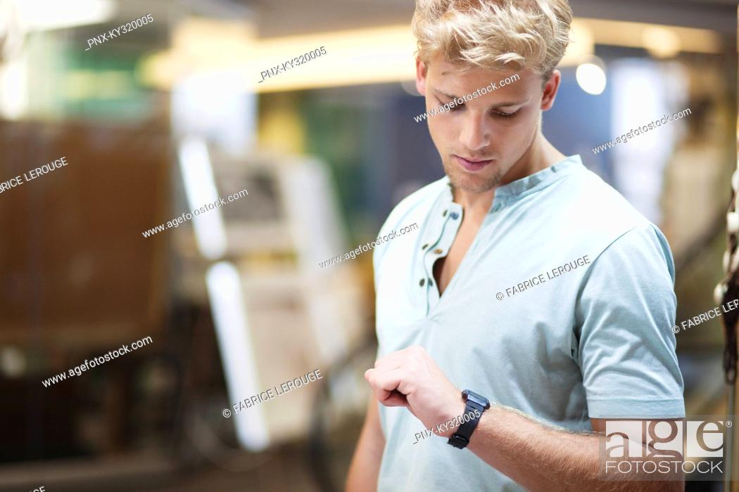 Stock Photo: Young man checking the time in a clothing store.
