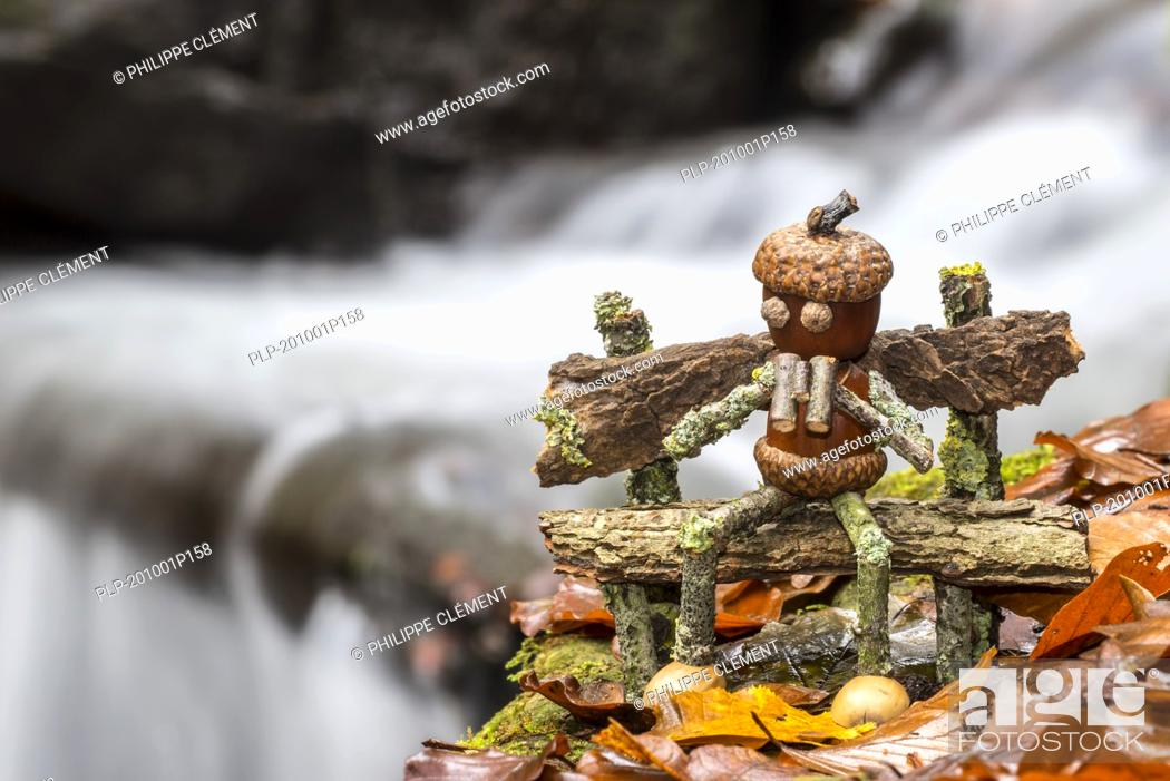 Stock Photo: Figure of little man / birdwatcher with binoculars made of acorns and twigs sitting on wooden bench next to waterfall along mountain stream in autumn.