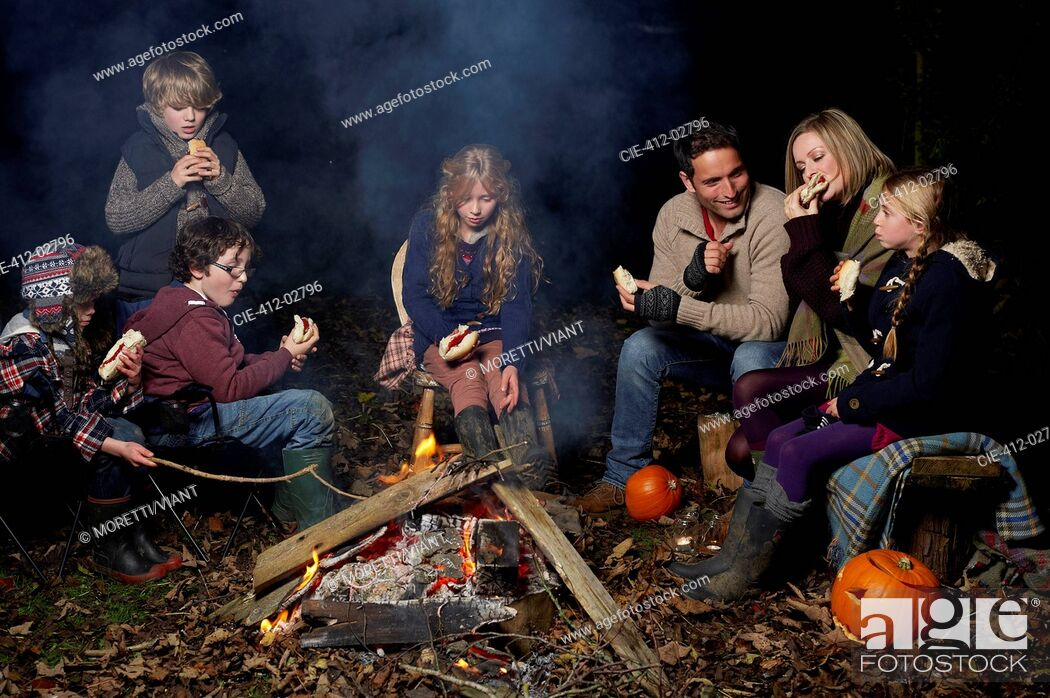 Imagen: Family eating around campfire at night.
