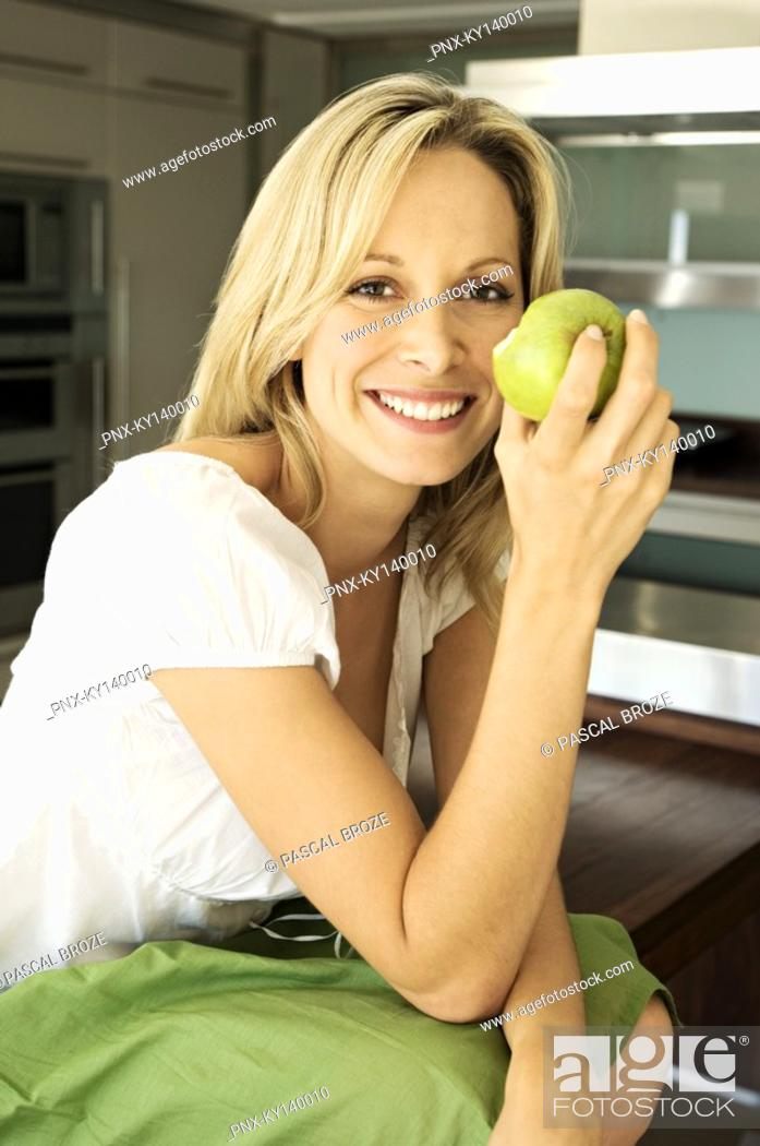 Stock Photo: Young smiling woman eating an apple.
