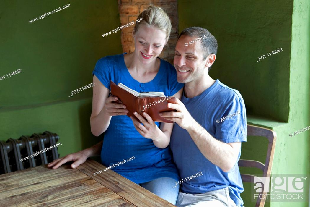 Stock Photo: A couple reading a personal organizer together and smiling.
