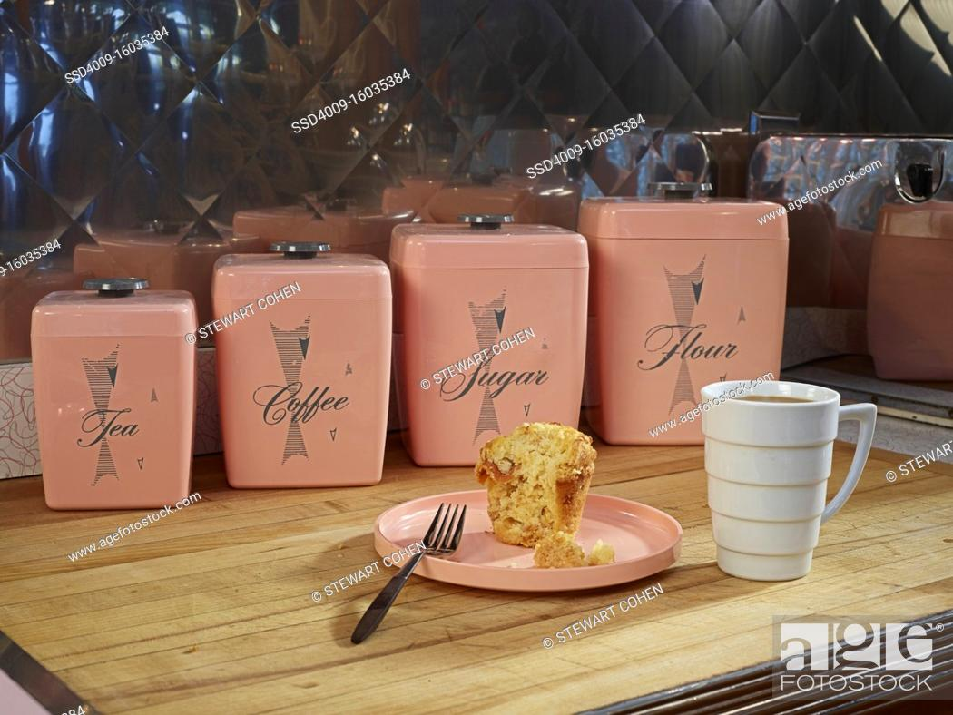 Stock Photo: Coffee and muffin on countertop in front of vintage, kitchen canisters.