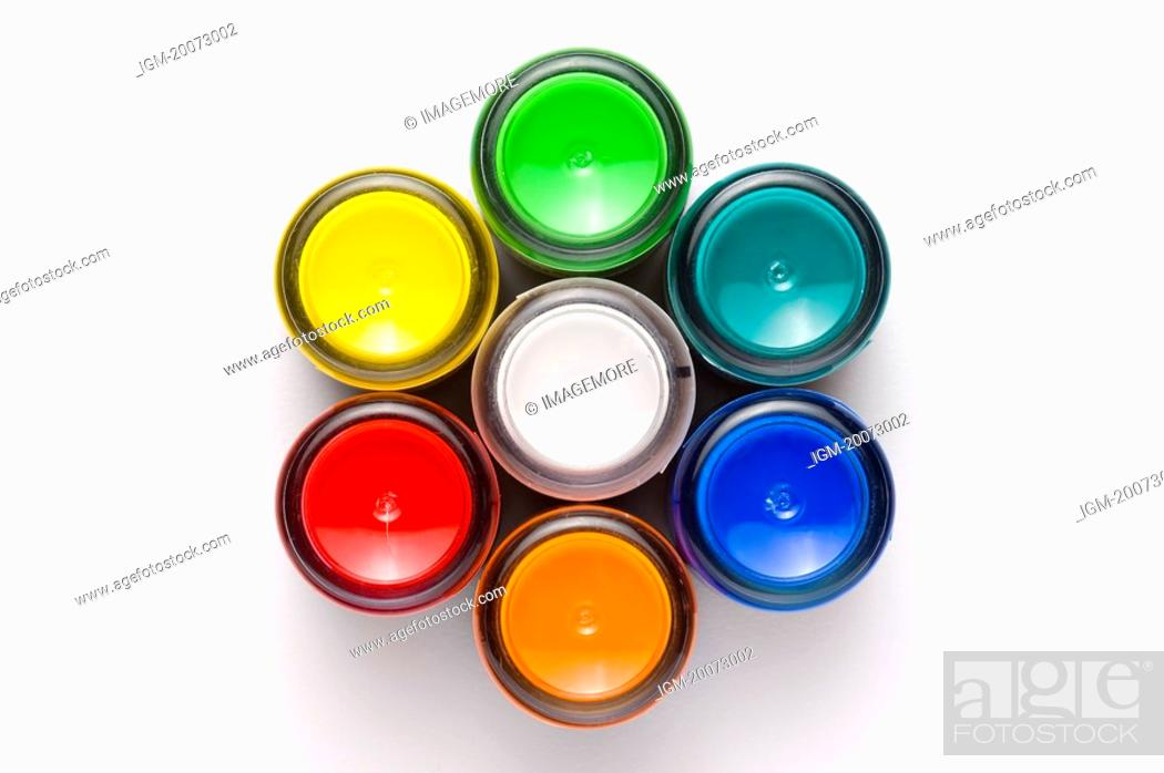 Stock Photo: Different colors of paint in jars forming a flower shape.