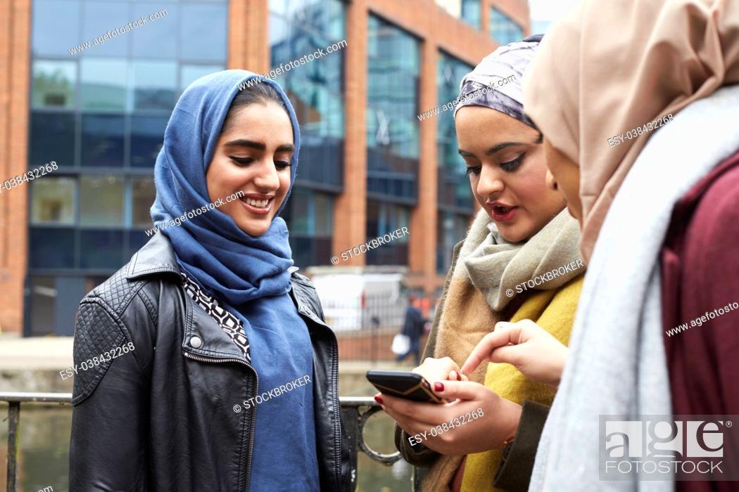 Stock Photo: Muslim Female Friends Using Mobile Phone In Urban Setting.