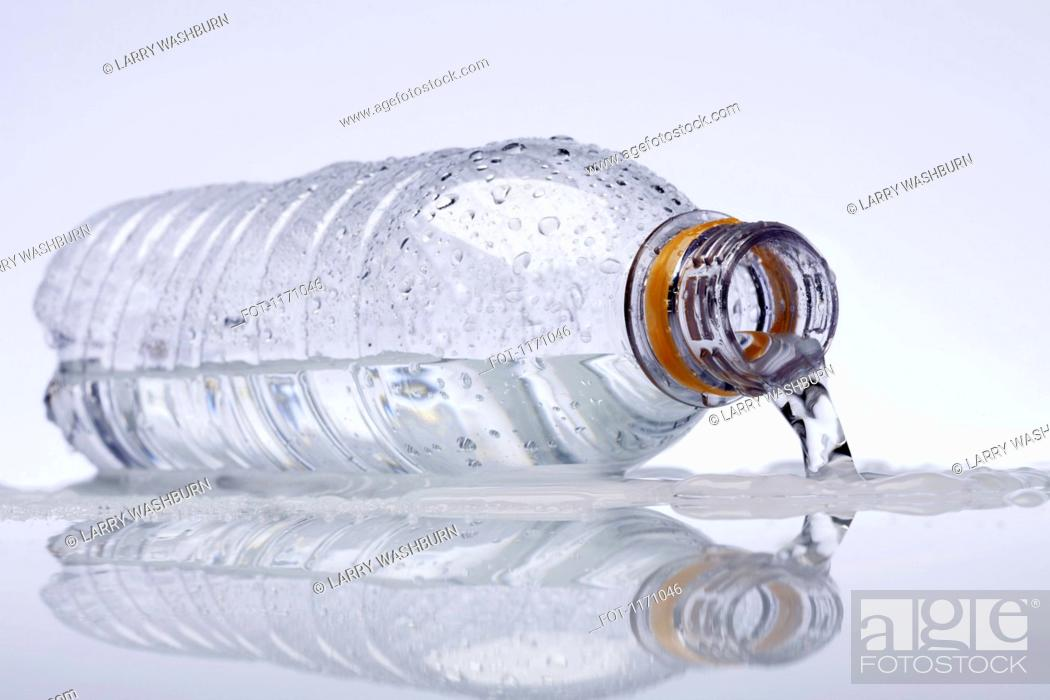 Stock Photo: A plastic water bottle lying on its side, water spilling out.