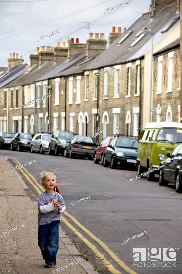 Stock Photo: a young boy walks down the street with a stick, cambridge united kingdom.
