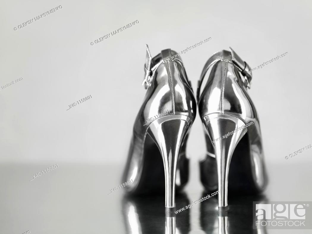 Stock Photo: Stylish shiny silver stiletto high heel shoes staning on metal surface.