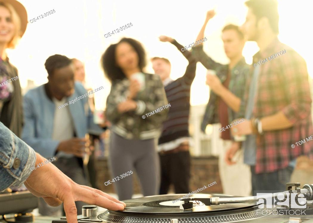 Imagen: DJ spinning record at rooftop party.