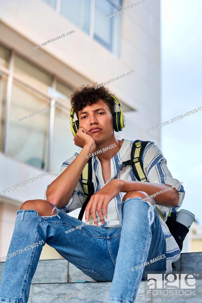 Stock Photo: Boring young afro with headphones on sitting on the street.