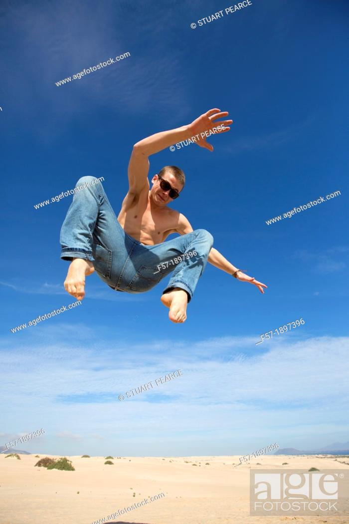 Stock Photo: Teenage boy jumping in the air over the dunes.