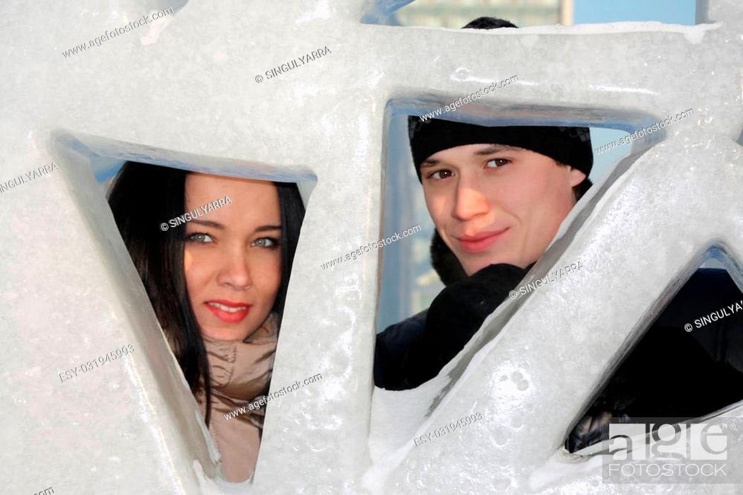 Stock Photo: Boy and girl peep through triangular holes in big ice wall at winter day.