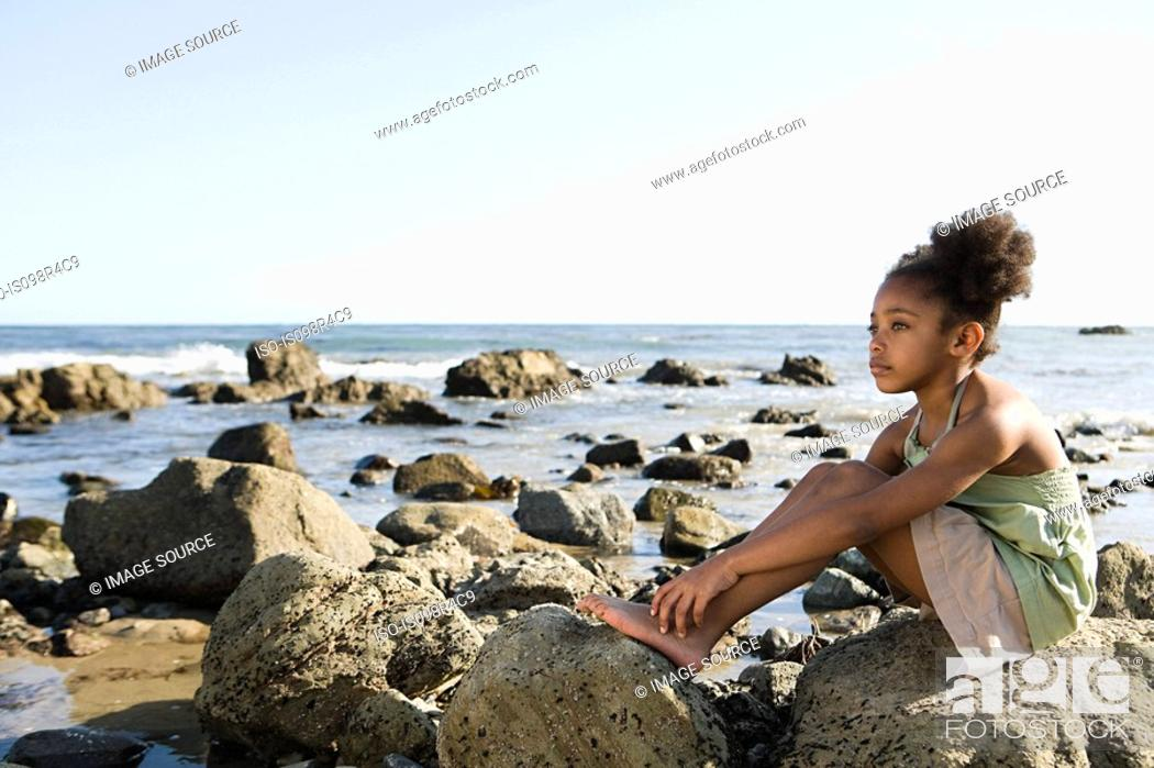 Stock Photo: Girl sitting on rocks at the beach.