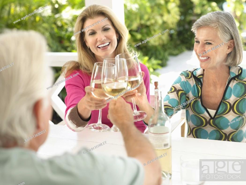 Stock Photo: Three people toasting with wine glasses sitting at verandah table.