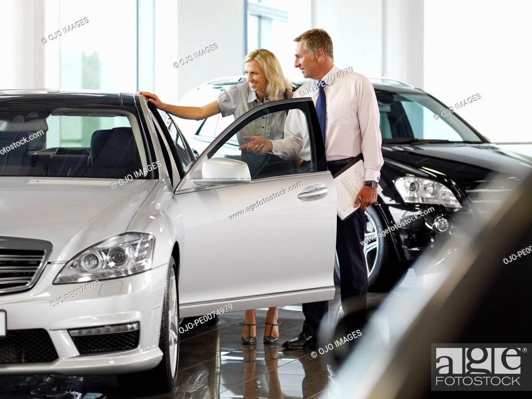 Stock Photo: Salesman talking to woman in automobile showroom.