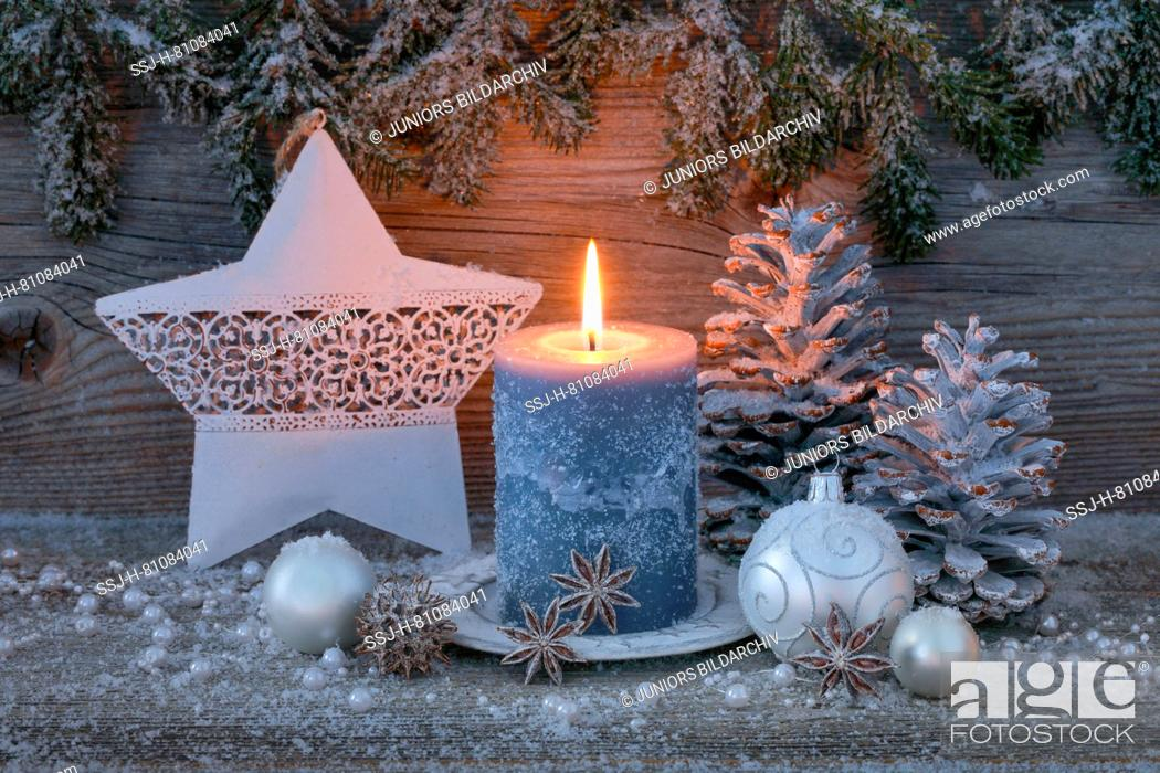 Stock Photo: Christmas decoration: Burning candle with silver christmas baubles, cones and a star. Switzerland.