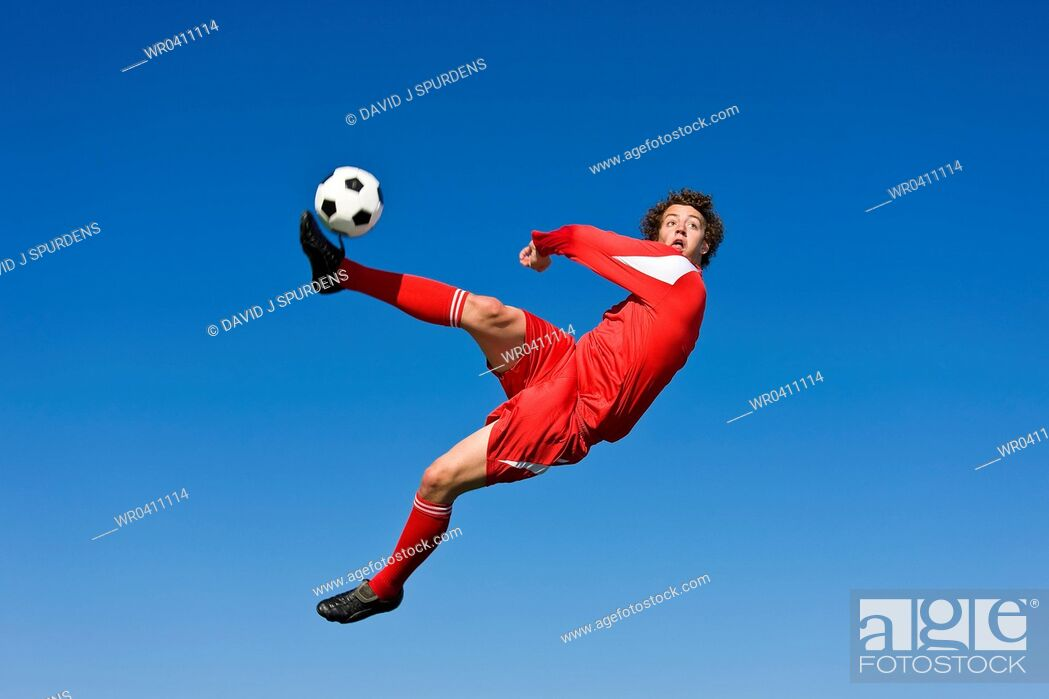 Stock Photo: A soccer player volleys the ball.