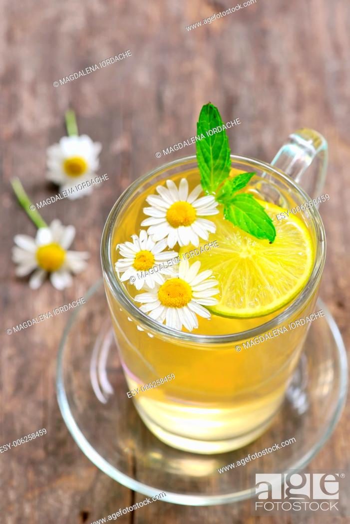 Stock Photo: Herbal tea with fresh chamomile flowers and lemon on wooden background.