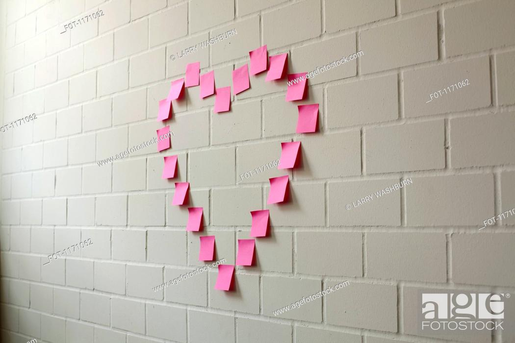 Stock Photo: Blank adhesive notes arranged into the shape of a heart on a brick wall.