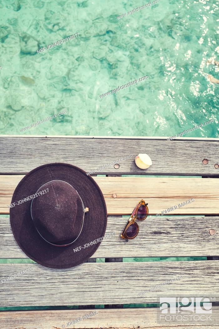 Stock Photo: Hat, sunglasses, shell on jetty.