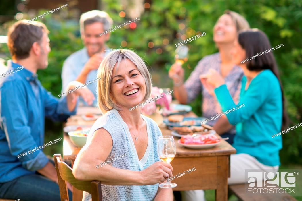 Stock Photo: Looking at the camera a beautiful woman in her forties with a wine glass by hand. She sits around a table in a garden with friends for dinner.