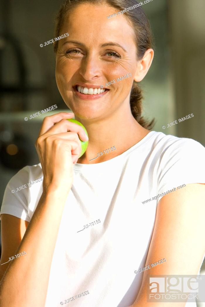Stock Photo: Woman with apple, smiling, portrait, close-up.