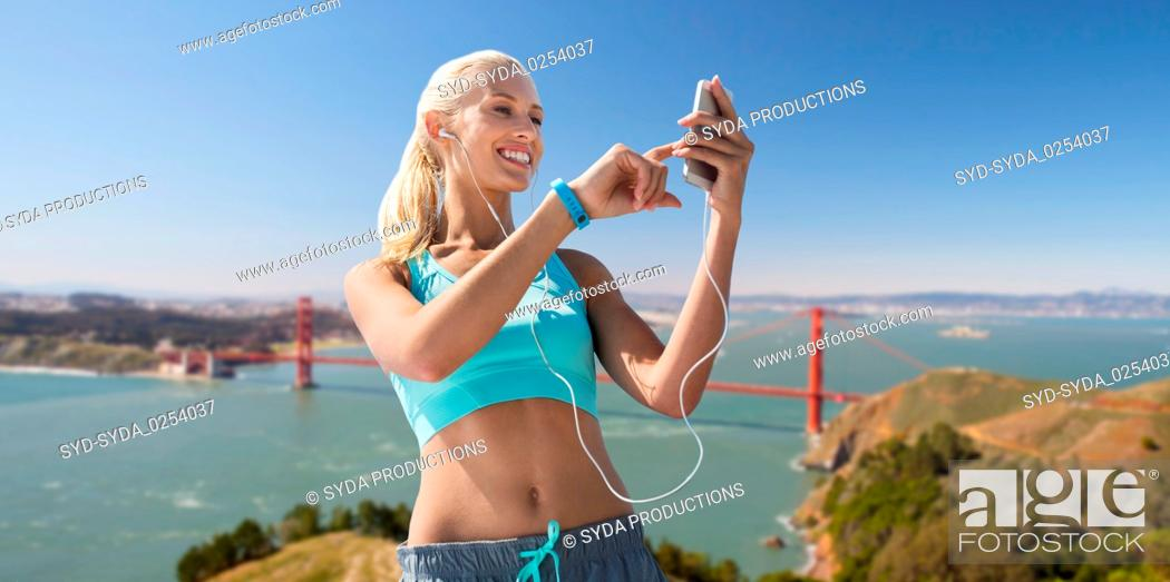Imagen: woman with smartphone and earphones doing sports.