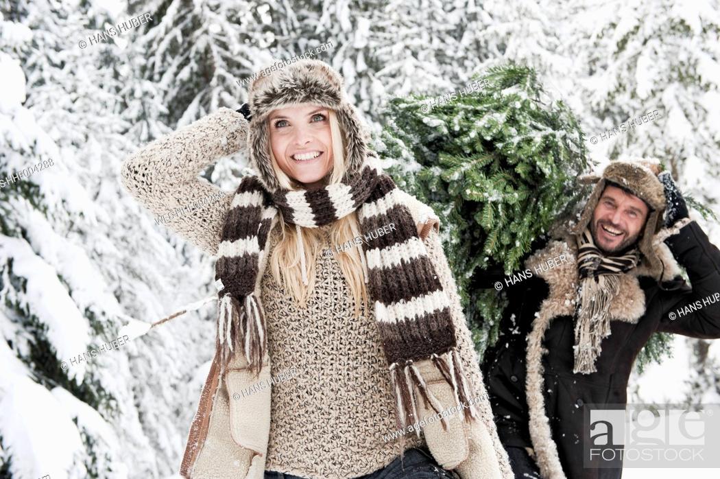 Stock Photo: Austria, Salzburg County, Man and woman walking through snow while man carrying christmas tree.