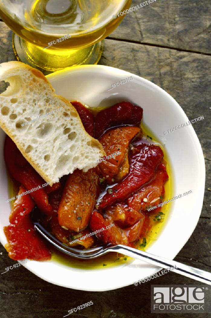 Stock Photo: Marinated red peppers with olive oil and white bread.