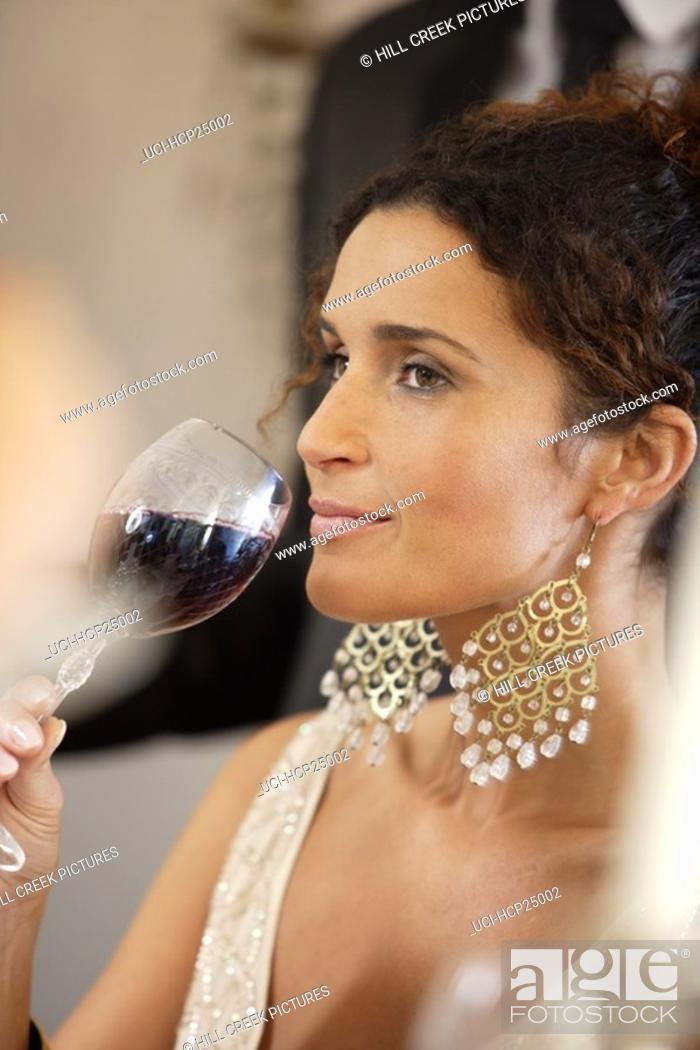 Stock Photo: Woman drinking wine at dinner party.