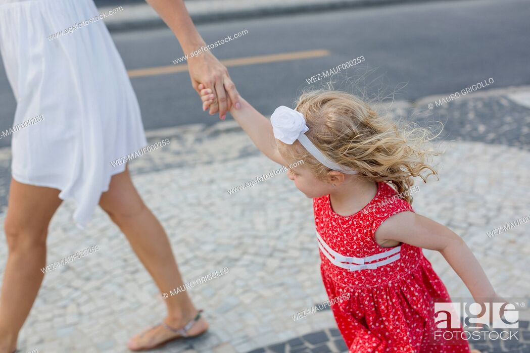 Imagen: Mother and daughter walking hand in hand.