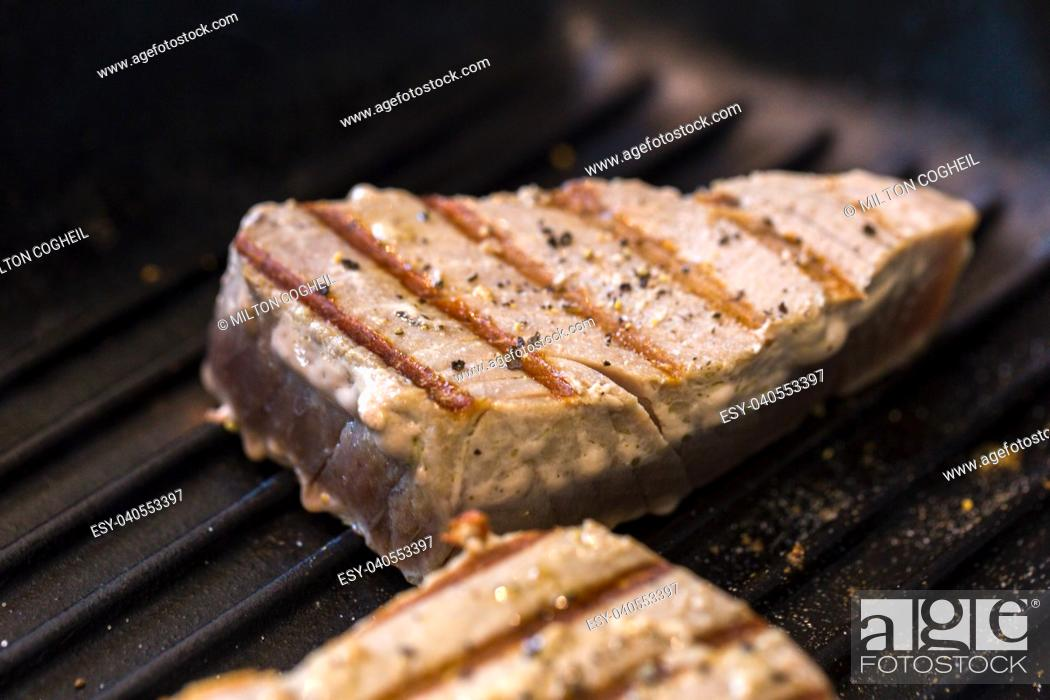 Stock Photo: Close up of chargrilled tuna steaks cooking in a griddle pan with seasoning.