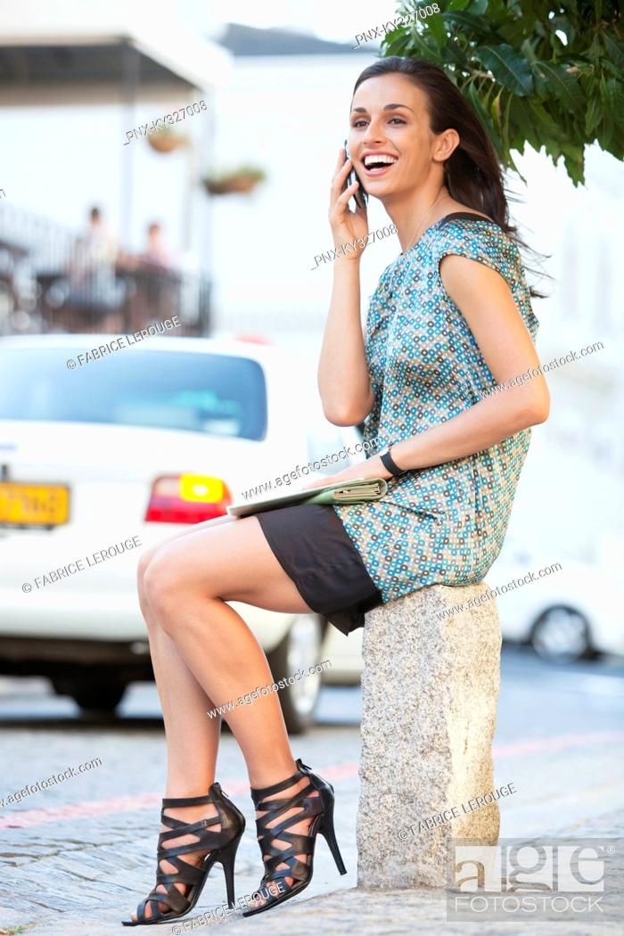 Stock Photo: Young woman talking on a mobile phone and smiling.