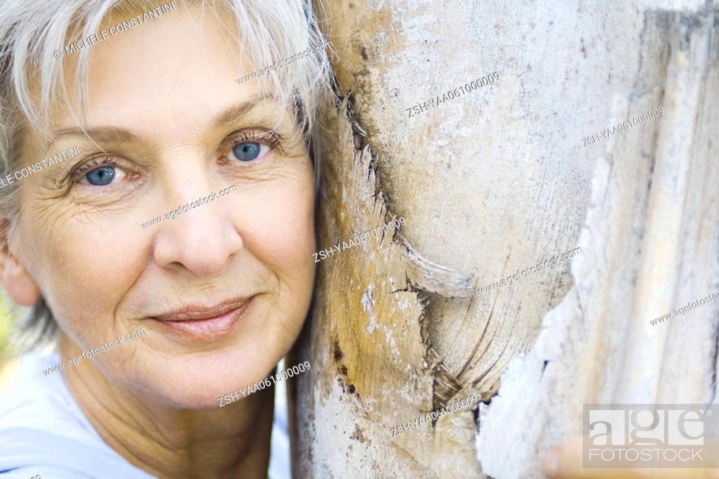Stock Photo: Senior woman leaning against tree trunk, smiling at camera, portrait.