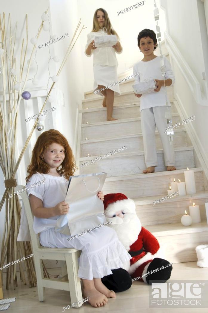 Stock Photo: Three children offering Christmas presents, indoors.