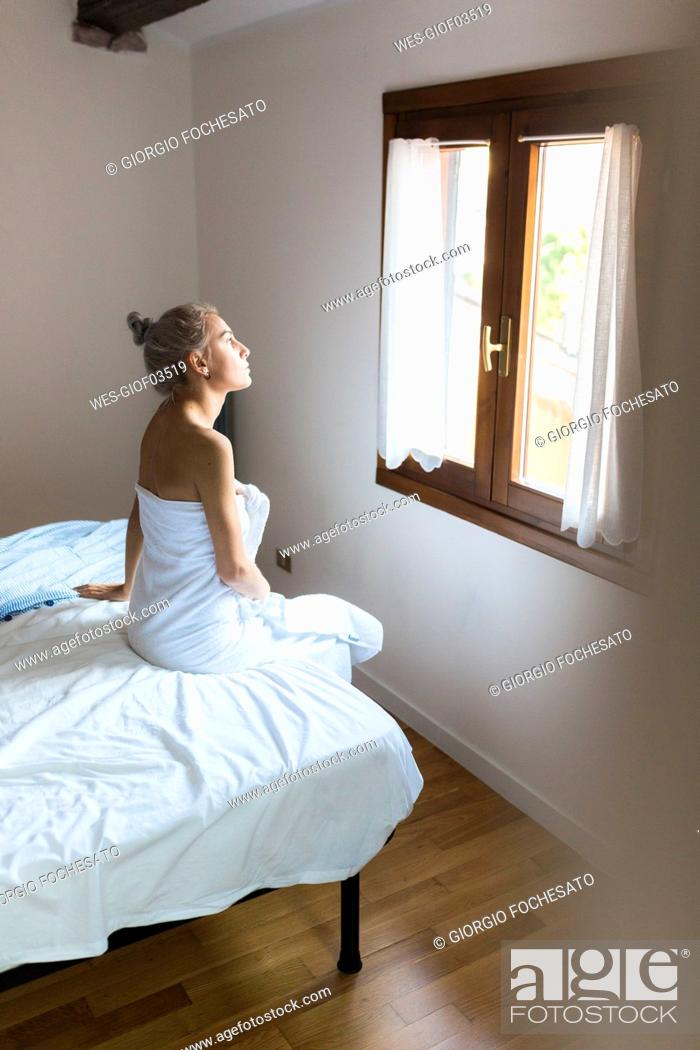 Stock Photo: Young woman wrapped in a towel sitting on bed looking out of window.