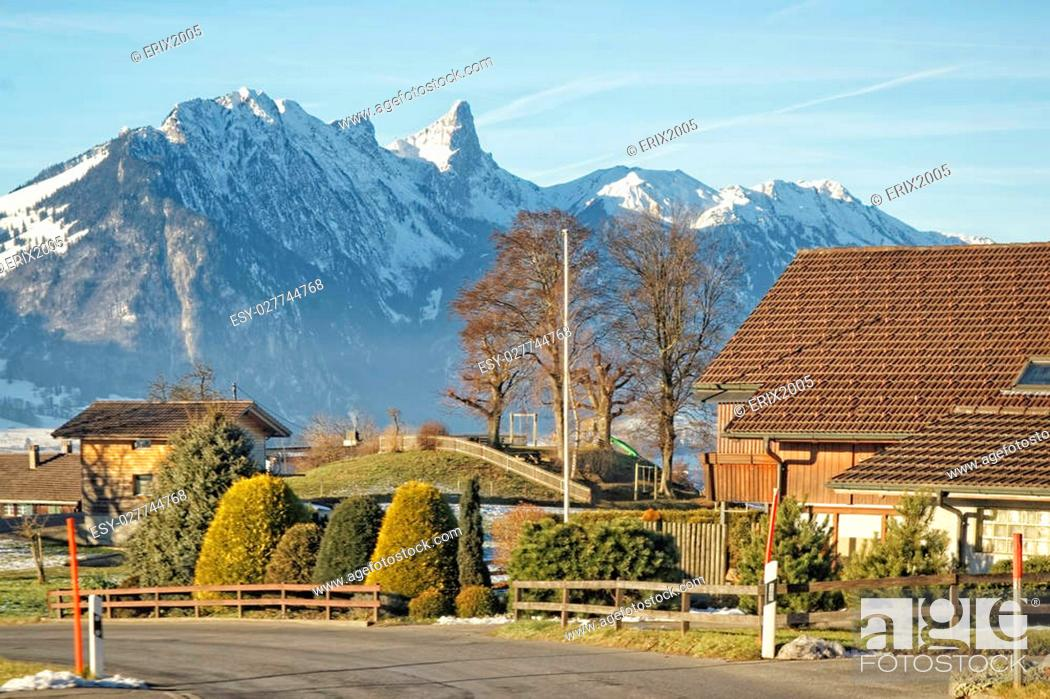 Stock Photo: A village with a view to the Swiss Alps mountains near the Thun lake in winter.
