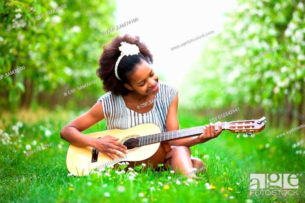 Stock Photo: Outdoor portrait of a young beautiful african american woman playing guitar - Black people.