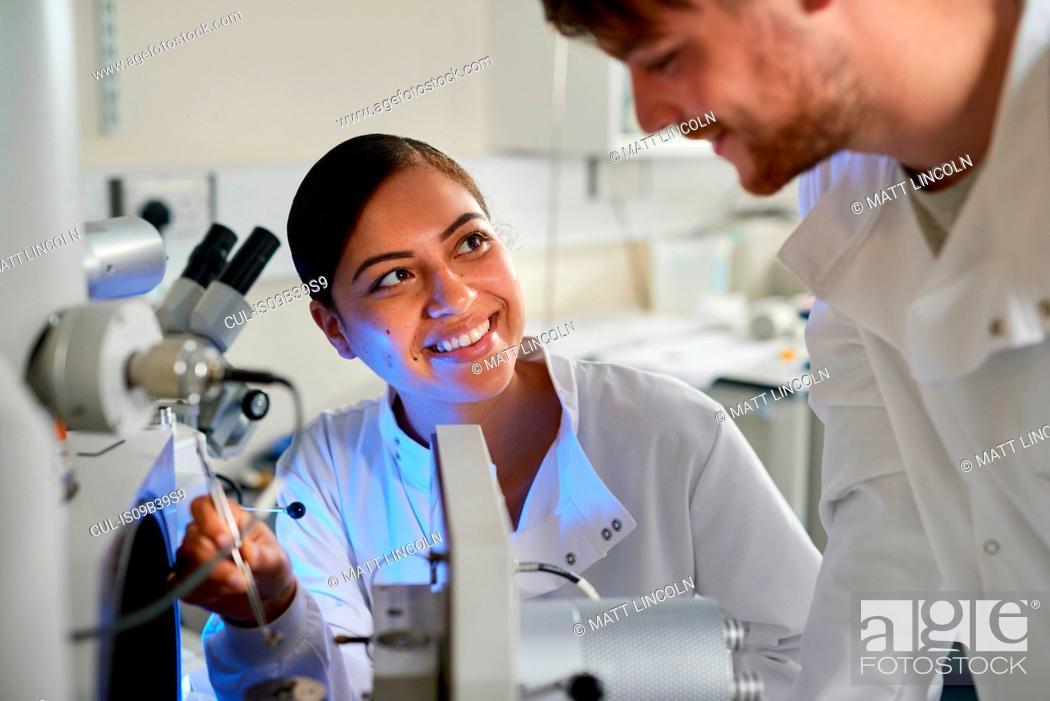 Stock Photo: Scientists in laboratory using scientific equipment smiling.