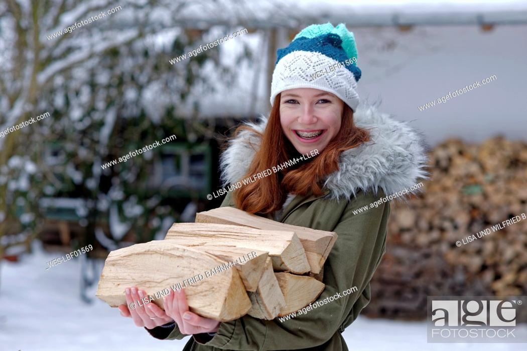 Stock Photo: Portrait of smiling teenage girl carrying firewood in winter.