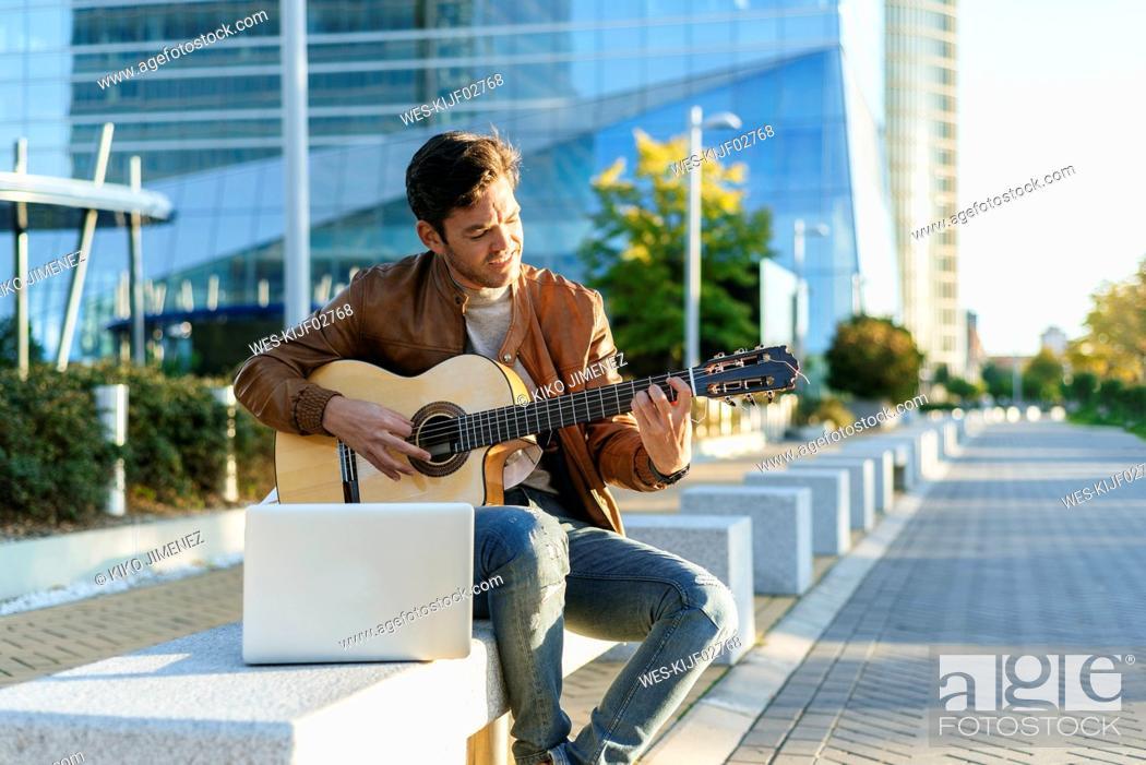 Imagen: Man with laptop playing guitar in the city, Madrid, Spain.