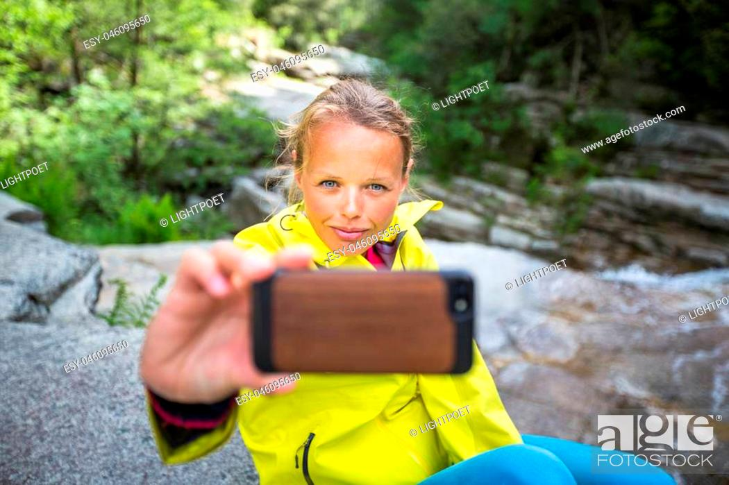 Stock Photo: Pretty, young female hiker taking a selfie while outdoors on a hike, taking a break near a mountain stream (shallow DOF).