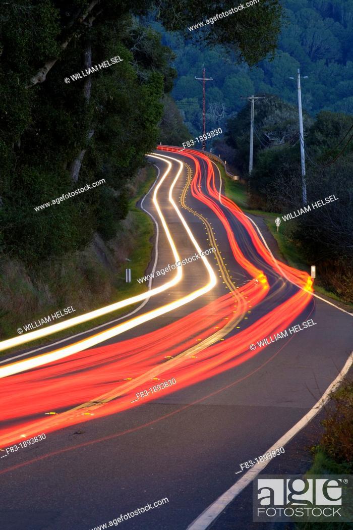 Stock Photo: Point Reyes-Petaluma Road, Marin County, California, USA, with car headlight and tail light streaks at dusk.