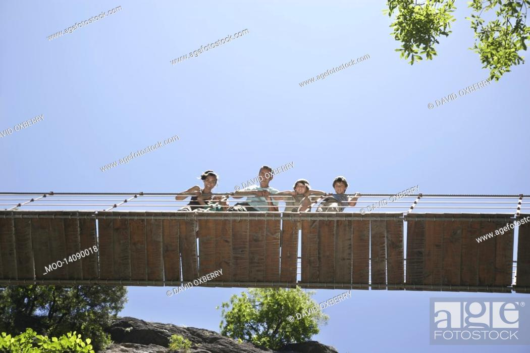 Stock Photo: Parents and two sons 7-12 on bridge looking down.