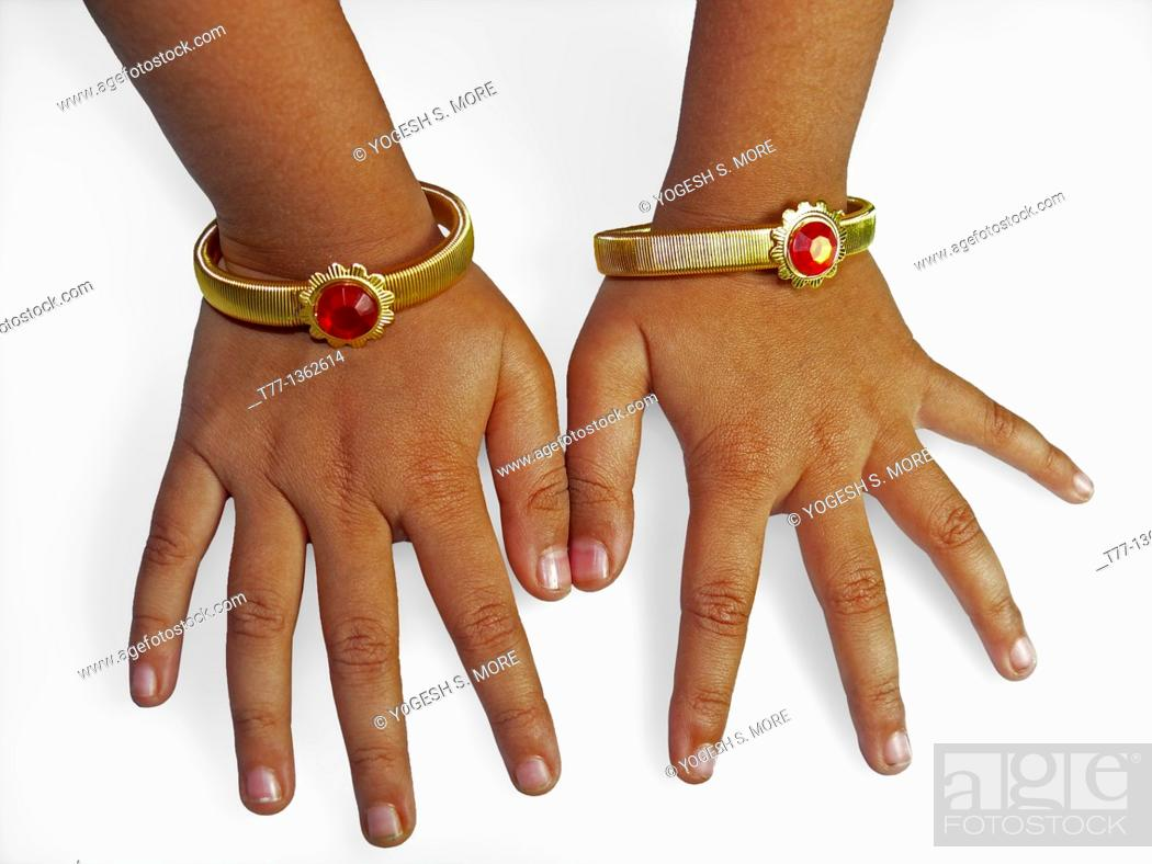 Stock Photo: Two gold bracelets in girl's hand, Maharashtra, India.