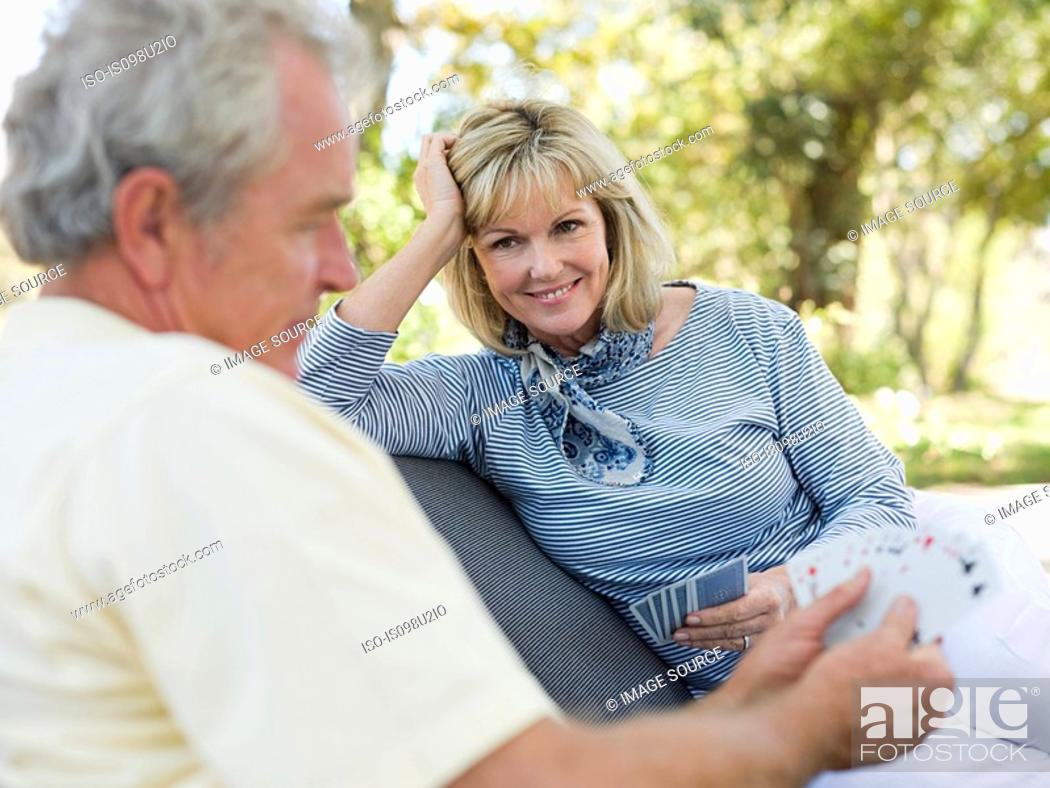 Stock Photo: Mature couple playing cards outdoors.
