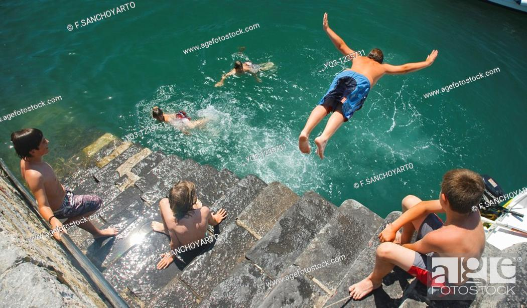 Stock Photo: Children diving in, Castro Urdiales, Cantabria, Spain.