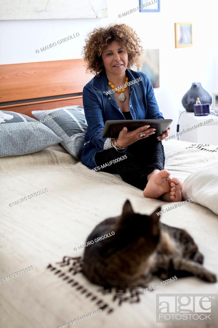 Stock Photo: Woman with cat on bed holding digital tablet.