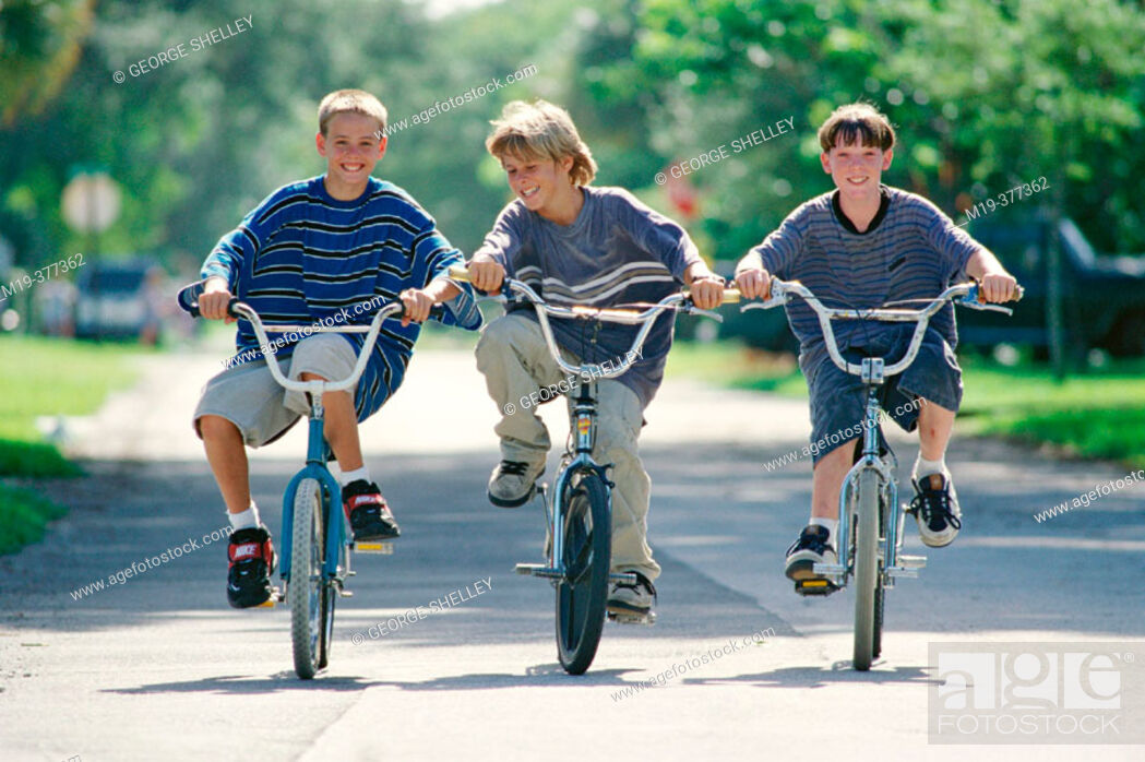 Stock Photo: three kids riding their bikes.
