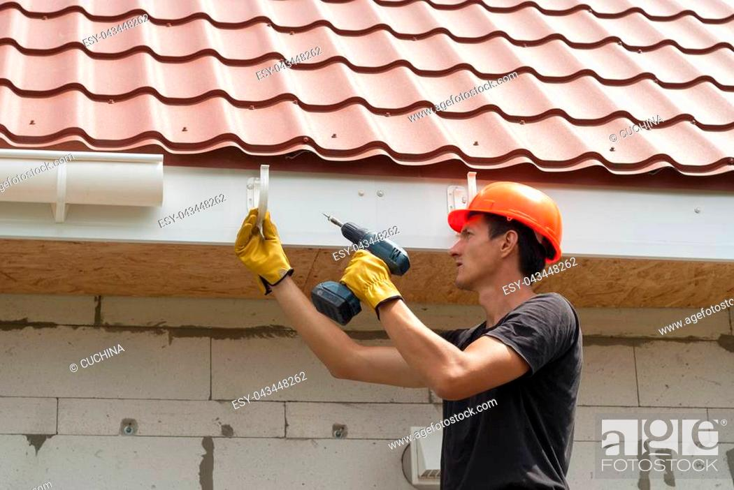 Stock Photo: worker installs the gutter system on the roof.